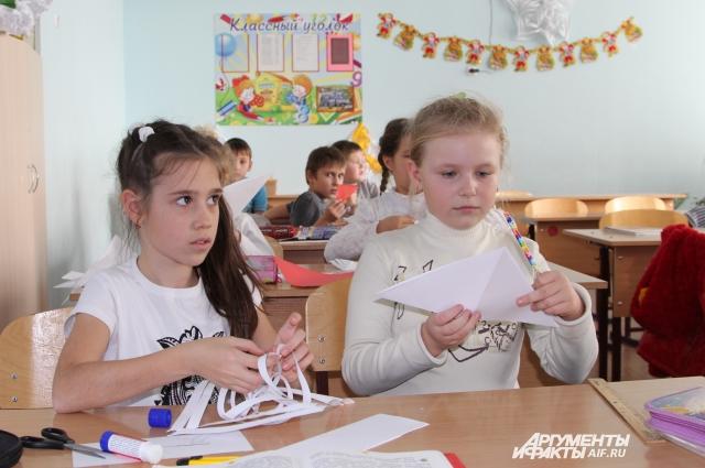 Маша Иващенко (справа) вырезает снежинку и думает, что вернётся домой после Нового года