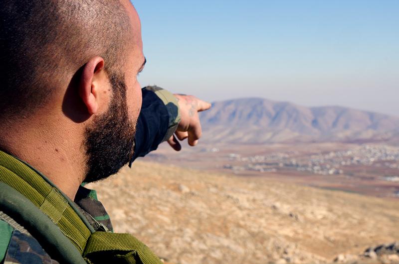 Солдат указывает на монастырь, подступы к которому охраняет добровольческий отряд. Всего в нескольких километрах от позиций отряда находятся деревни, подконтрольные боевикам