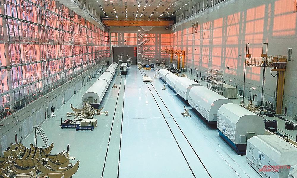 В корпусах монтажно-испытательного комплекса, где собирают ракету и спутники.