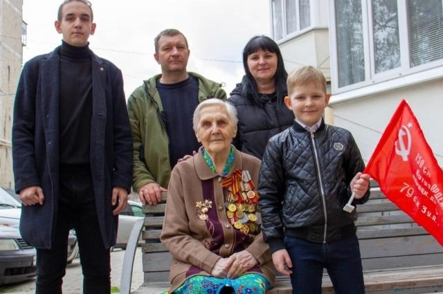Ветеран с комсомольцами, которые её навещают.