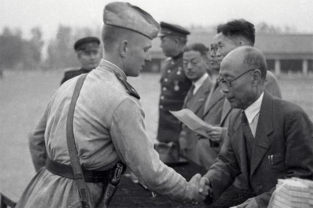 Председатель президиума Верховного Народного собрания КНДР Ким Ду Бон  вручает медали