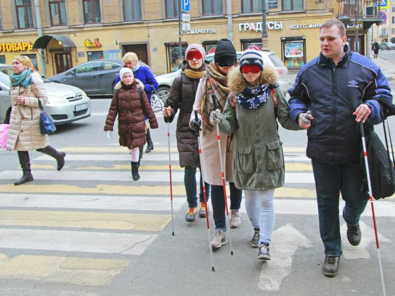 Алексей уверенно переводит людей через дорогу.