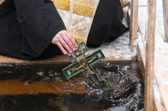 Священник трижды опускает в купель крест.