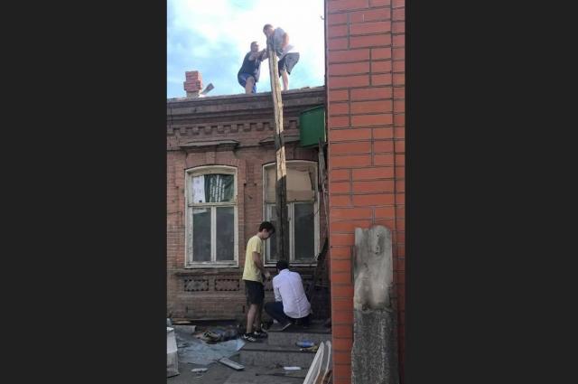 Рабочие разбирают крышу.