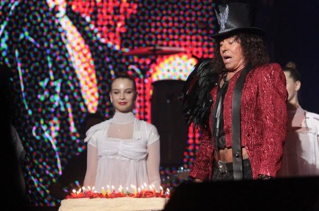 Леонтьев задувает свечи на праздничном торте.