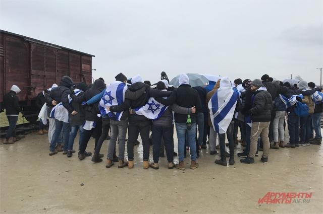 У вагона без окон напутях вБиркенау стоят израильтяне. Завернувшись внациональные флаги, они поют еврейскую поминальную молитву– кадиш.