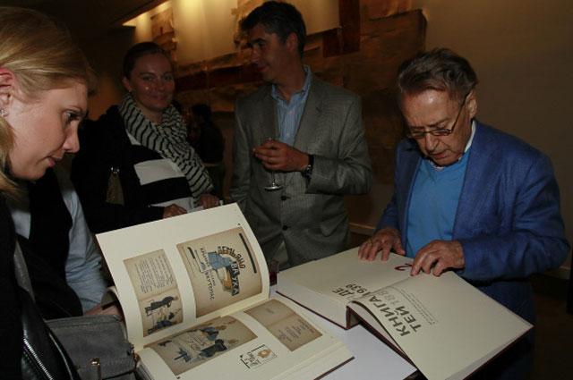 Андрей Дементьев рассматривает Книгу для детей на официальном открытии выставки Экспериментальное искусство детской иллюстрации в России (ХХ-ХХI век) в Нью-Йорке. 2012 год
