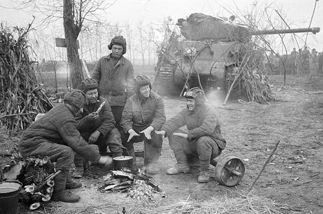 Танкисты отдыхают около костра, рядом танк «Шерман», поставленный по ленд-лизу США. 1-й Прибалтийский фронт, 1944 г.
