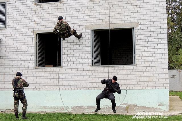 Во время штурма здания бойцы поочерёдно ловко спускались по тросам с крыши.