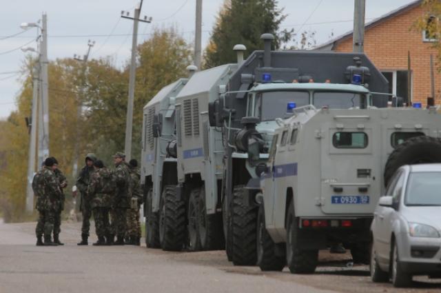 Сотрудники правоохранительных органов стоят в оцеплении на одной из улиц деревни Тимошкино.