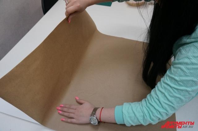 Начинаем приклеивать бумагу с одного края, аккуратно разглаживая по направлению в стороны.