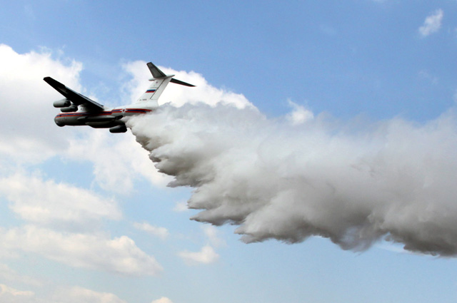 Самолет МЧС Ил-76 производит сброс воды над очагом пожара во время показных тактико-специальных учений по ликвидации лесо-торфяных пожаров.