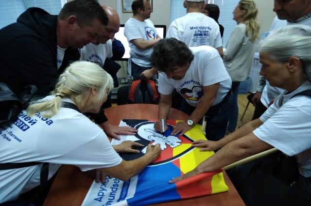 Участники автопробега подарили Дому дружбы народов Татарстана флаг со своими автографами.