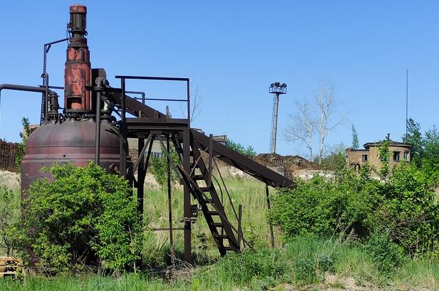 Заброшенные установки и оборудование зарастают зеленью.