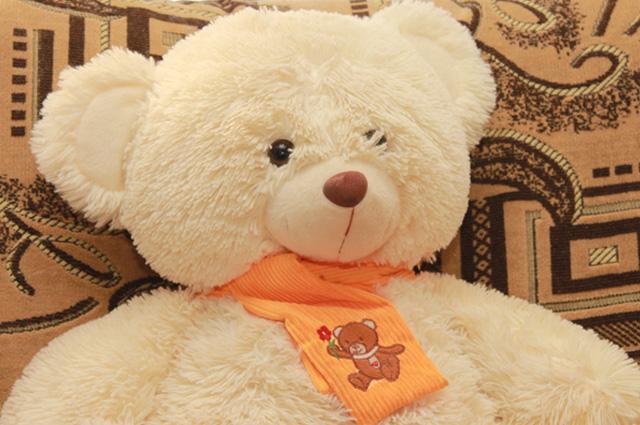 Медведь заботливо укутан шарфом, чтобы не простыл