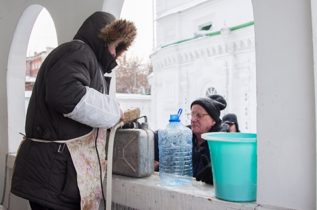 Верующие набирают воду канистрами.