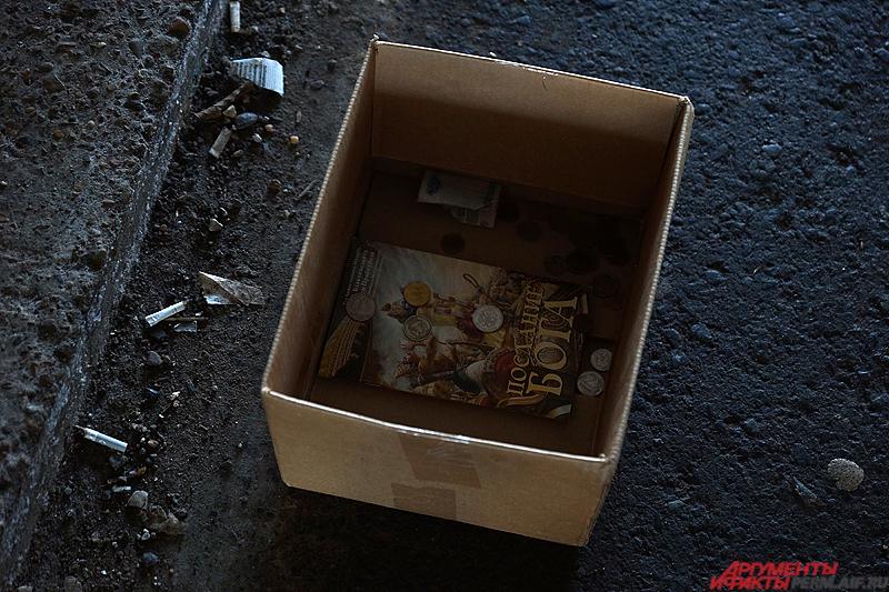 Рядом стоит картонная коробка, куда проходящие мимо люди кидают мелочь.