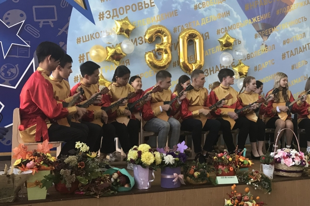 Дети разных национальностях играют на балалайках в школьном оркестре