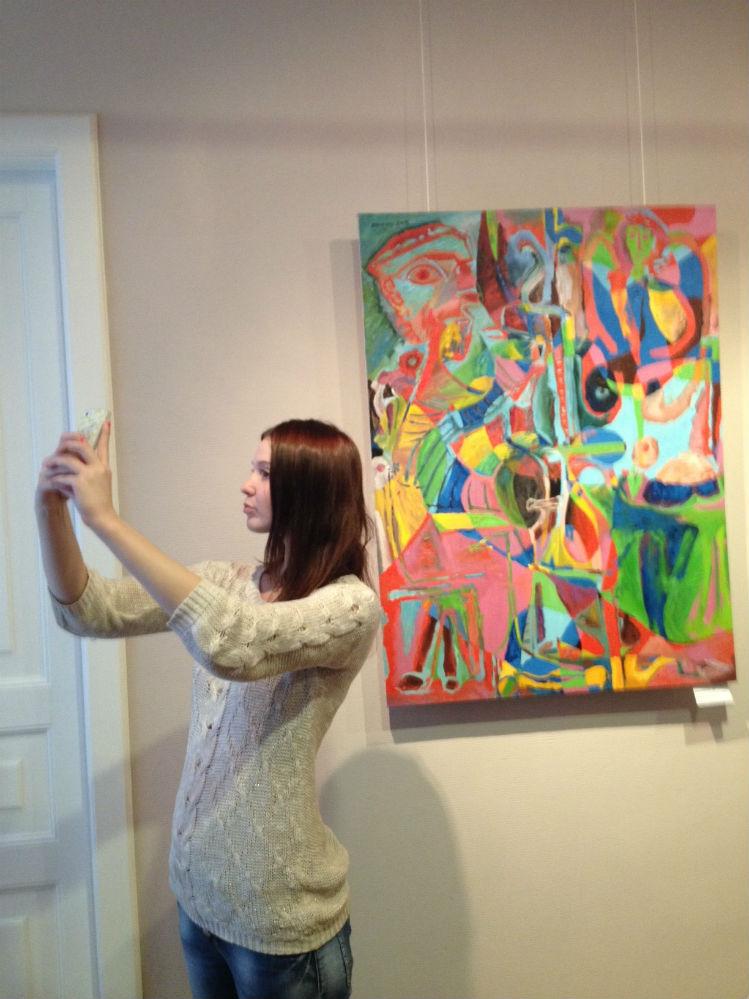 Селфи на фоне работ художника делают молодые посетители музея.
