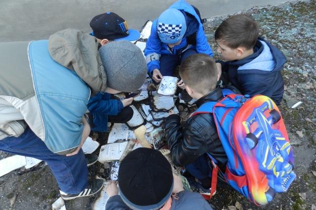 Школьники подбирают выпавшие из окна кабинета информатики обгоревшие книги и тетради.