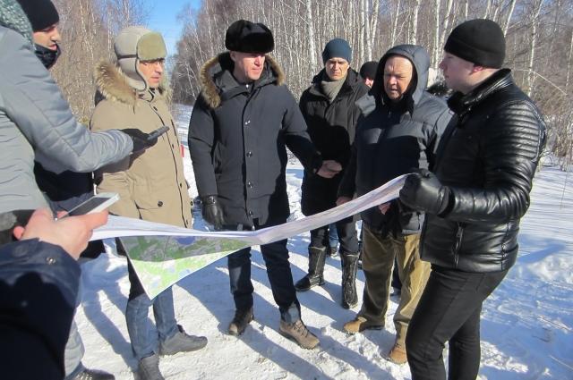 Руслан Кухарук изучает карту геодезистов: полигон находится ниже домов, поэтому подтопления не произойдет.