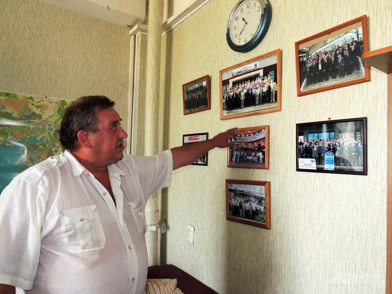 На стене офиса детектива висят памятные фотографии, грамоты и свидетельства