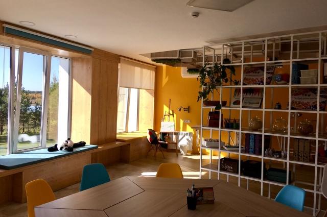 Пространство для арт-терапии с большими окнами, чтобы в помещение попадало как можно больше естественного света.