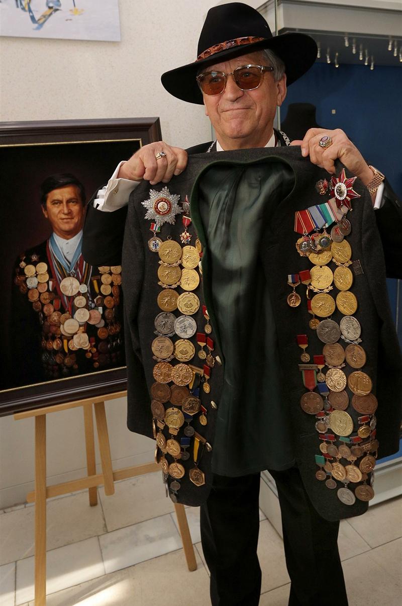 Александр Тихонов держит свой пиджак с медалями весом 18 кг