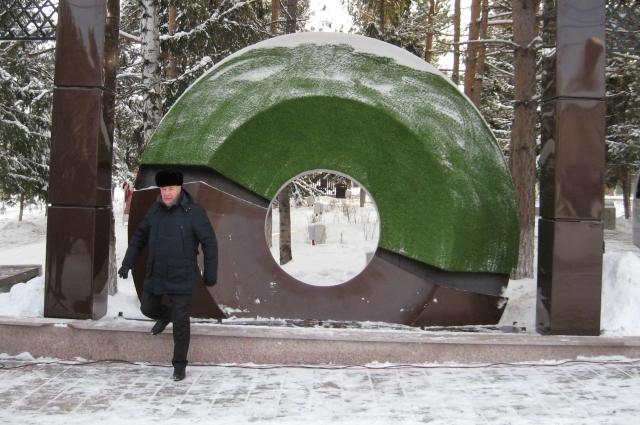 Огромное колесо от ротора шагающего экскаватора - бурое снизу, как символ труда угольщиков, и зелёное сверху, как символ заботы горняков о природе.