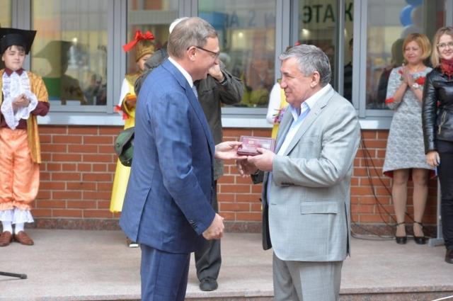 губернатор Александр Бурков вручает Борису Коваленко знак отличия «За служение Омской области» первой степени.