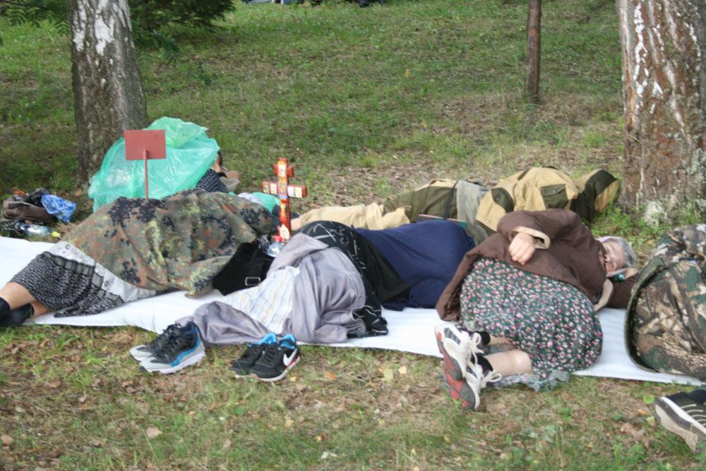 Усталые паломники уютно расположились на отдых прямо на газонах обители.