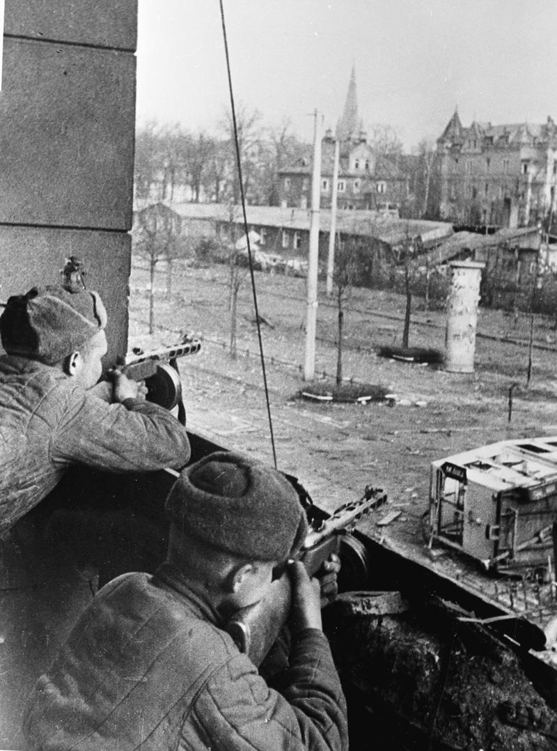 Советские бойцы ведут огонь во время боя на одной из улиц города Бреслау (Вроцлав). Май 1945 года.