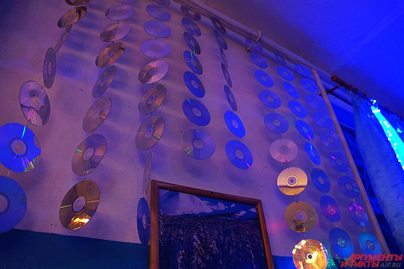 На стене поблескивают сотни компакт-дисков, изредка мерцающих от попадающего в них света