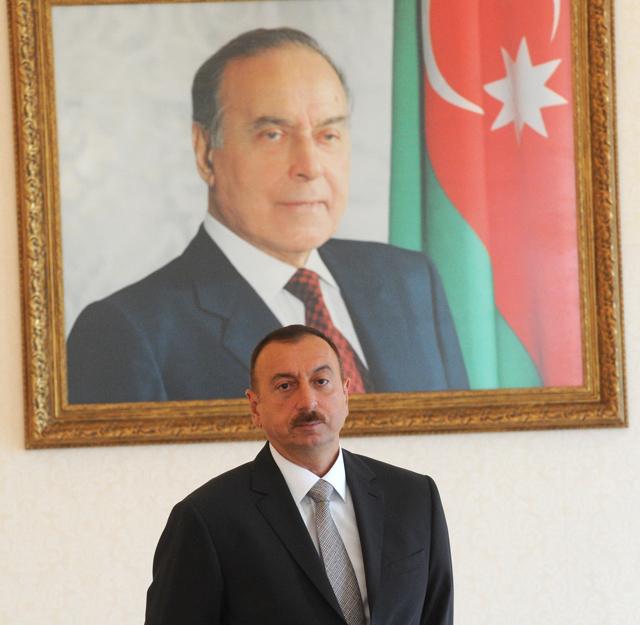 Ильхам Алиев у портрета своего отца, прежнего президента Азербайджана Гейдара Алиева.