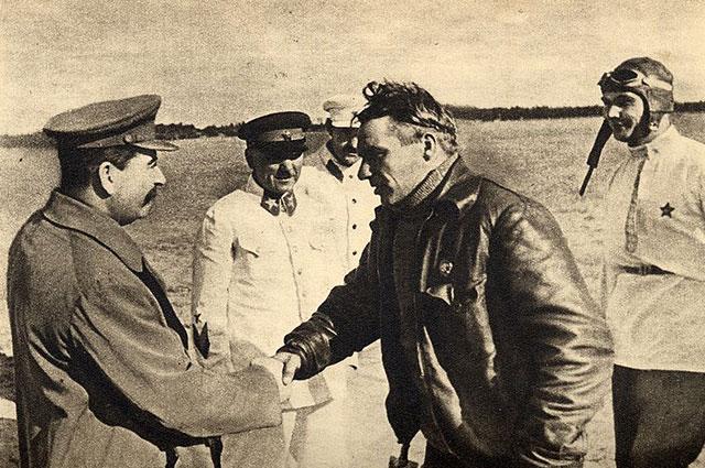 Встреча товарищей Чкалова, Байдукова и Белякова на Щёлковском аэродроме 10 августа 1936 года. Товарищ Сталин здоровается с тов. Чкаловым. Рядом стоят товарищи Ворошилов, Л. М. Каганович и Беляков.