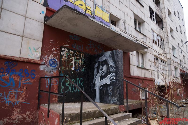 Стены многоэтажки изрисованы граффити.