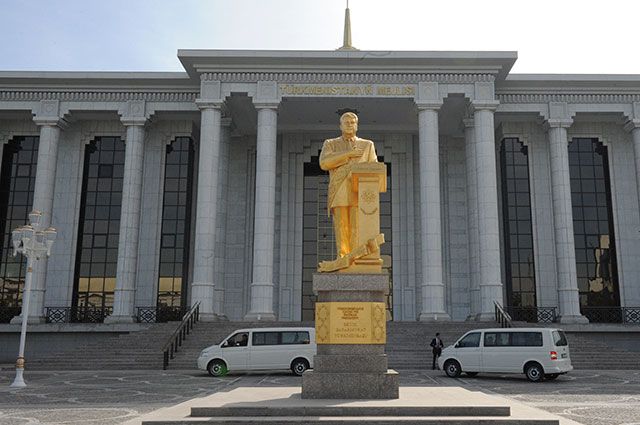 Здание Меджлиса Туркменистана в Ашхабаде. На первом плане - памятник первому президенту Туркменистана Сапармурату Ниязову.