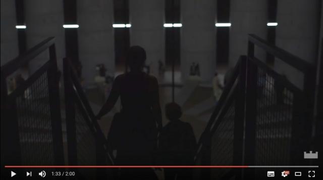 На кадре видео - посетители инсталляции; на заднем плане - колонны, в которых сидят плакальщики.