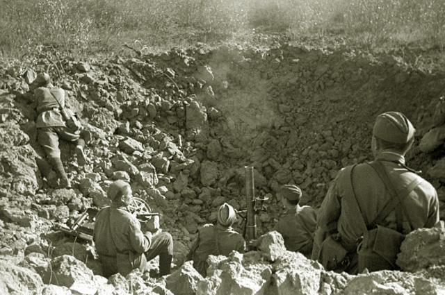 Солдаты ведут миномётный огонь из большой воронки от разорвавшегося снаряда. 1942 год