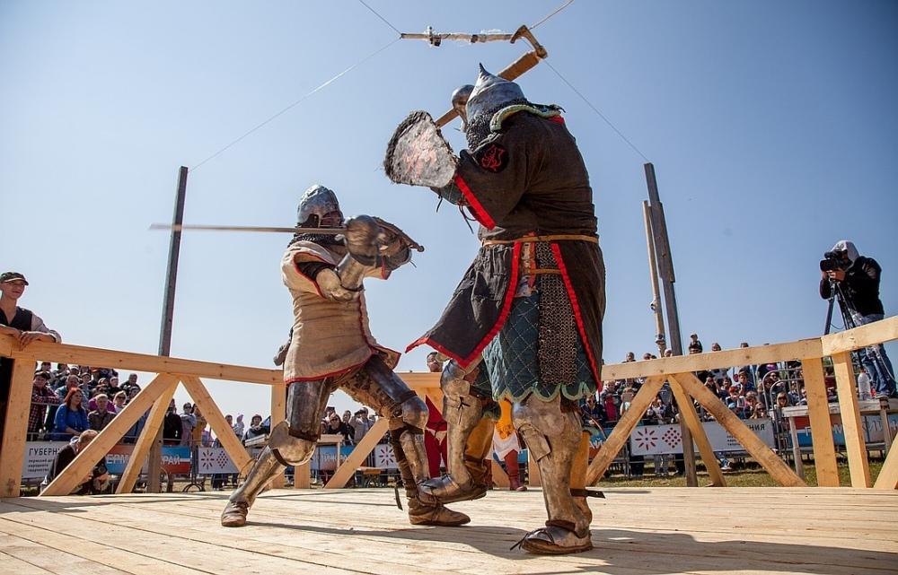 Бойцы в доспехах сражаются на мечах и топорах.