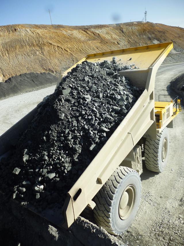 Из 200-тонного кузова летят в дробилку весьма приличные камни.