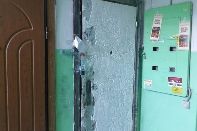 Искорёженная взрывной волной дверь, напоминает жильцам о том, что всё может повториться.