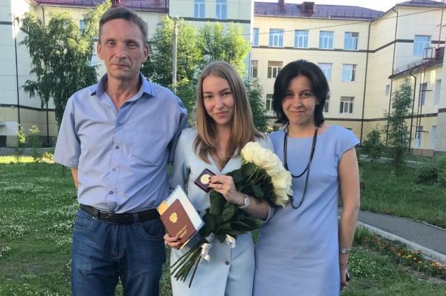 Евгения Симанова на выпускном со своими родителями.