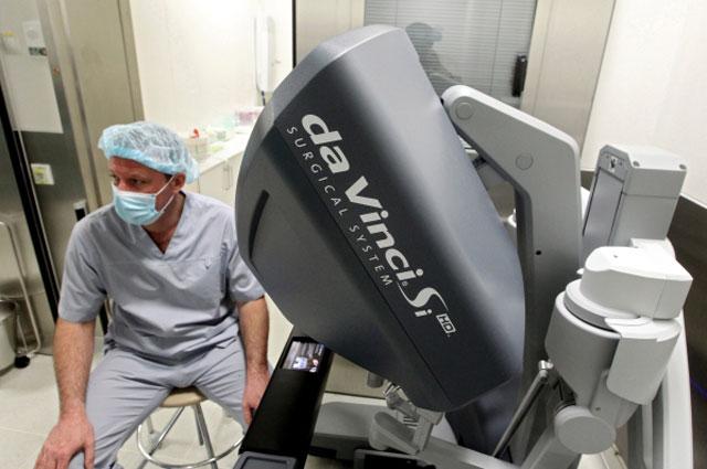 Хирург за пультом управления роботом Да Винчи в Медицинском центре
