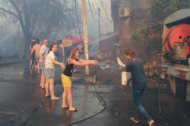Жители выстроились в живую цепь, поливая из вёдер дома.