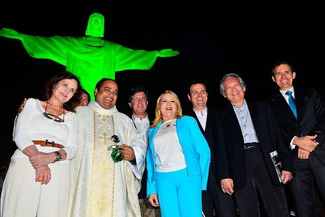 Люди собирались перед статуей Иисуса Христа, освещенной зеленым светом, в Национальный день борьбы с глаукомой.