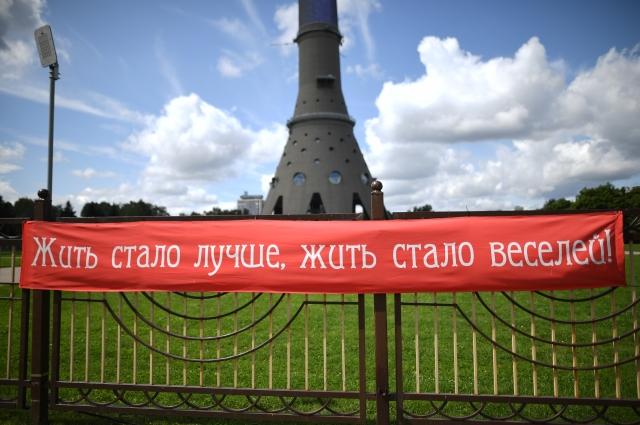 Плакат с надписью «Жить стало лучше, жить сало веселей!» в парке «Путешествие в юность» у Останкинской башни в Москве. 2019 г.