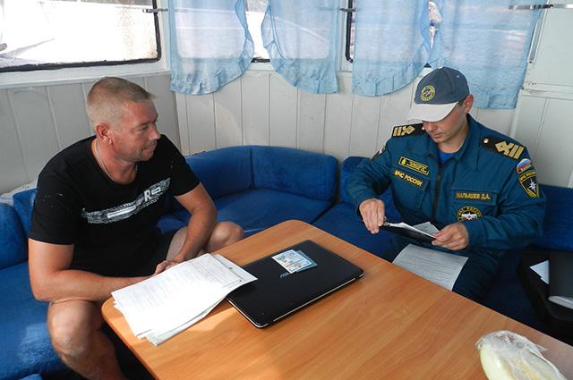 Денис Малышев выписывает штраф за перегруз на последнем катере.