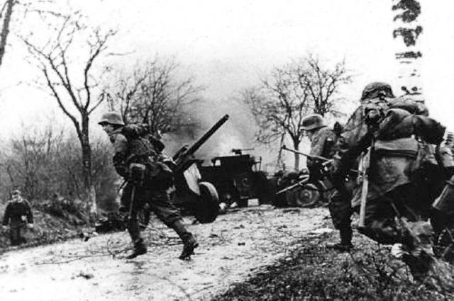 Немецкие солдаты, проходящие мимо брошенной американской техники
