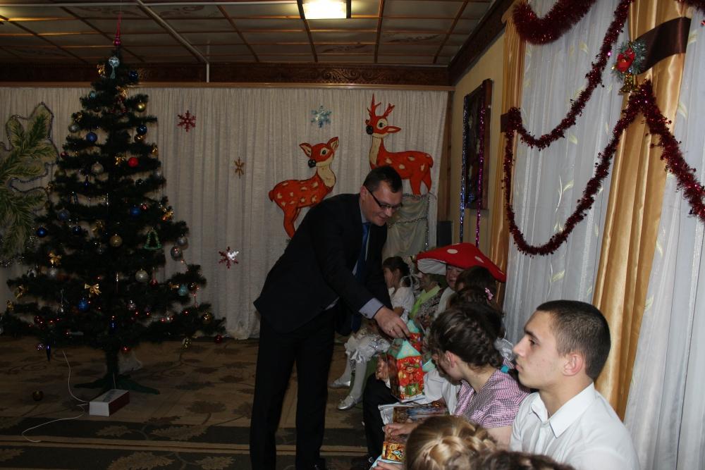 Дмитрий Данякин вручает подарки ребятишкам.